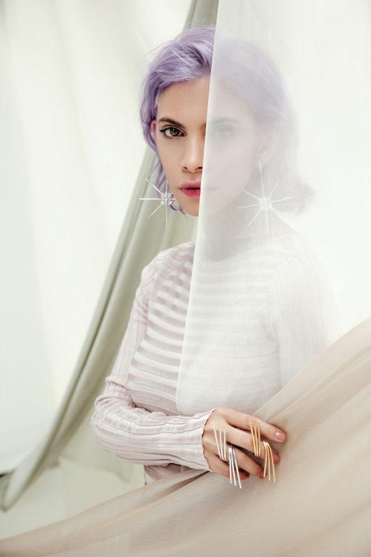 Modelo de pelo morado detrás de telas utilizando joyas de la colección no.5 de Aysha Bilgrami. Imagen de Campaña de Colección No.5 de Aysha Bilgrami Joyeria por Daniella Benedetti