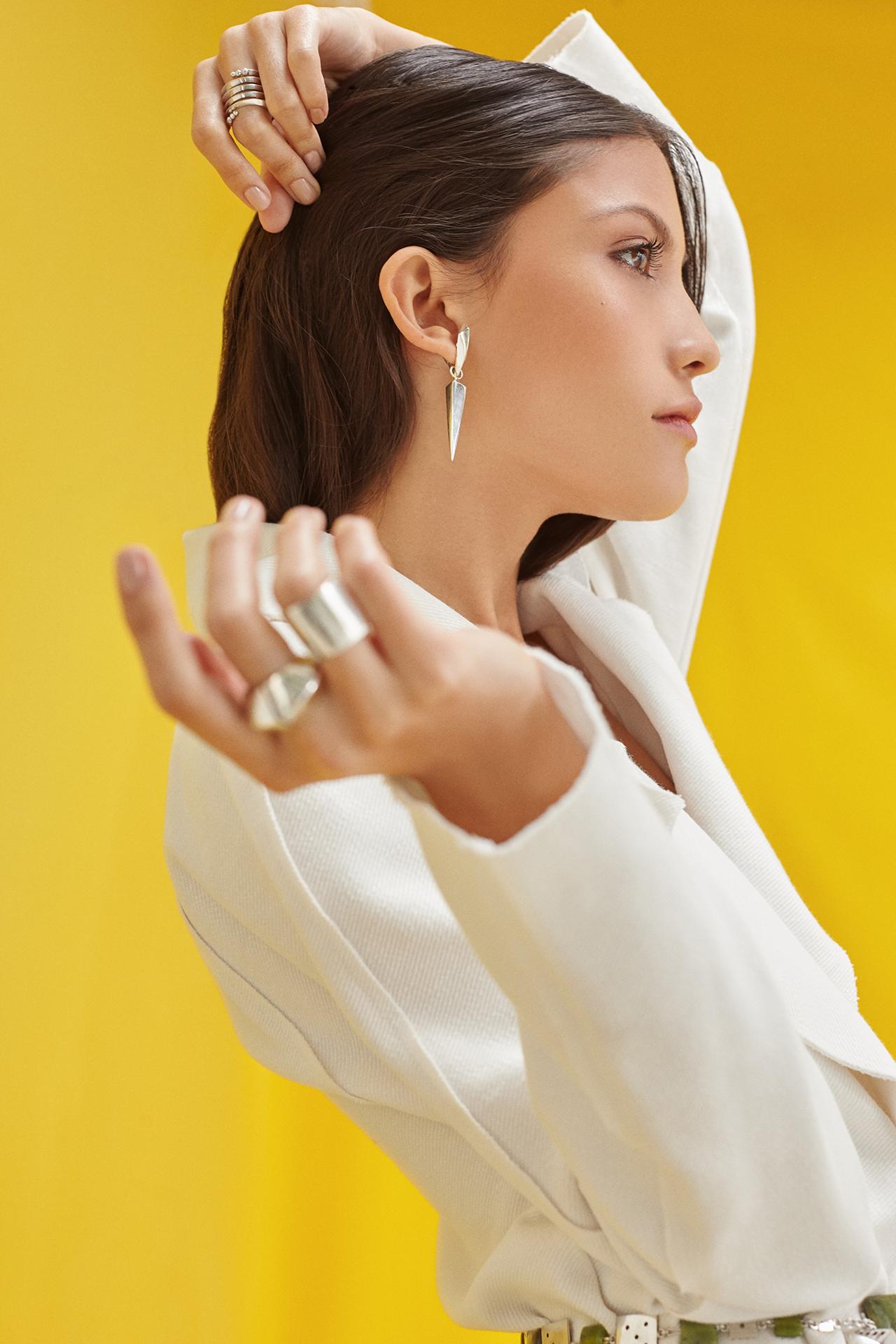 Modelo con chaqueta plateada, candongas con dijes piramidales plateados y anillos Parte de la Colección No.7 de Aysha Bilgrami Joyeria. Imagen de Campaña de Colección No.7  de Aysha Bilgrami Joyeria por Daniella Benedetti
