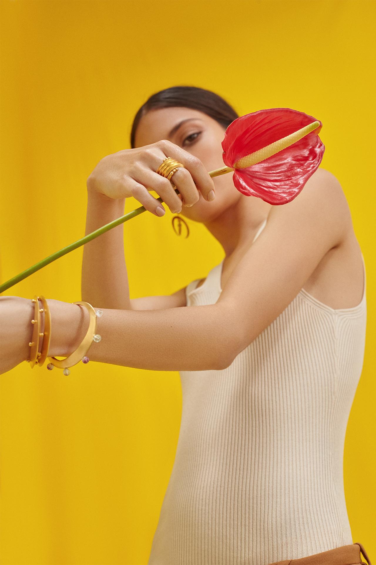 modelo con una flor, anturio rojo, pulseras doradas y anillos de de la Colección No.7 de Aysha Bilgrami Joyeria. Imagen de Campaña de Colección No.7  de Aysha Bilgrami Joyeria por Daniella Benedetti