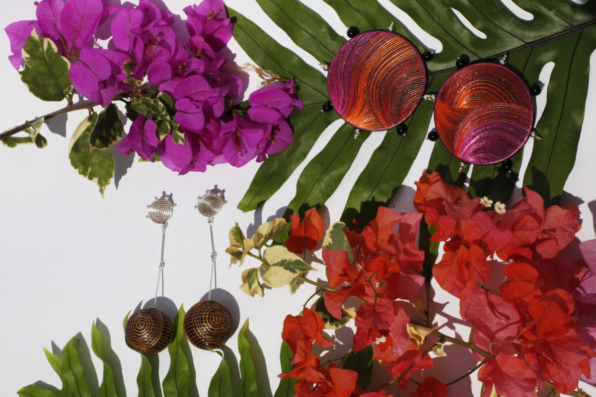 PINK AND ORANGE DISCO EARRINGS AND BINDU SILVER WITH PURPLE AND YELLOW SPIRAL TAMO EARRINGS EARRINGS MADE WITH THE ENCHAPE EN TAMO TECHNIQUE FROM PASTO IN A TROPICAL SETTING OF GREEN LEAVES AND PURPLE AND ORANGE BUGAMBILIAS.