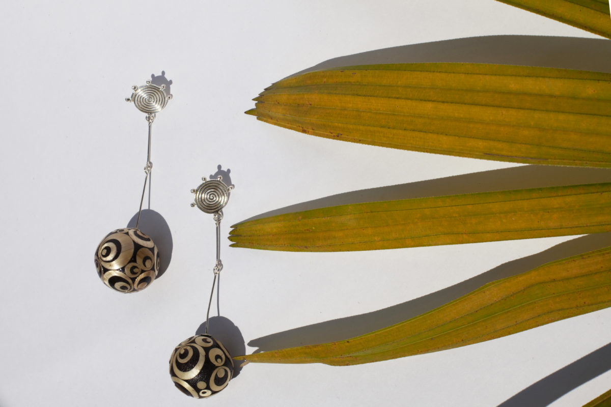 BINDU LONG EARRINGS MADE WITH THE ENCHAPE EN TAMO TECHNIQUE FROM PASTO AND SILVER IN A TROPICAL SETTING OF GREEN LEAVES