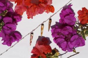 Tres Dijes piramidales en madera con enchape en Tamo, en un ambiente tropical de flores fucsias y naranjas, realizados por artesanos de Pasto, Nariño al sur de Colombia. Parte de la Colección cápsula de enchape en tamo de Aysha Bilgrami Joyeria