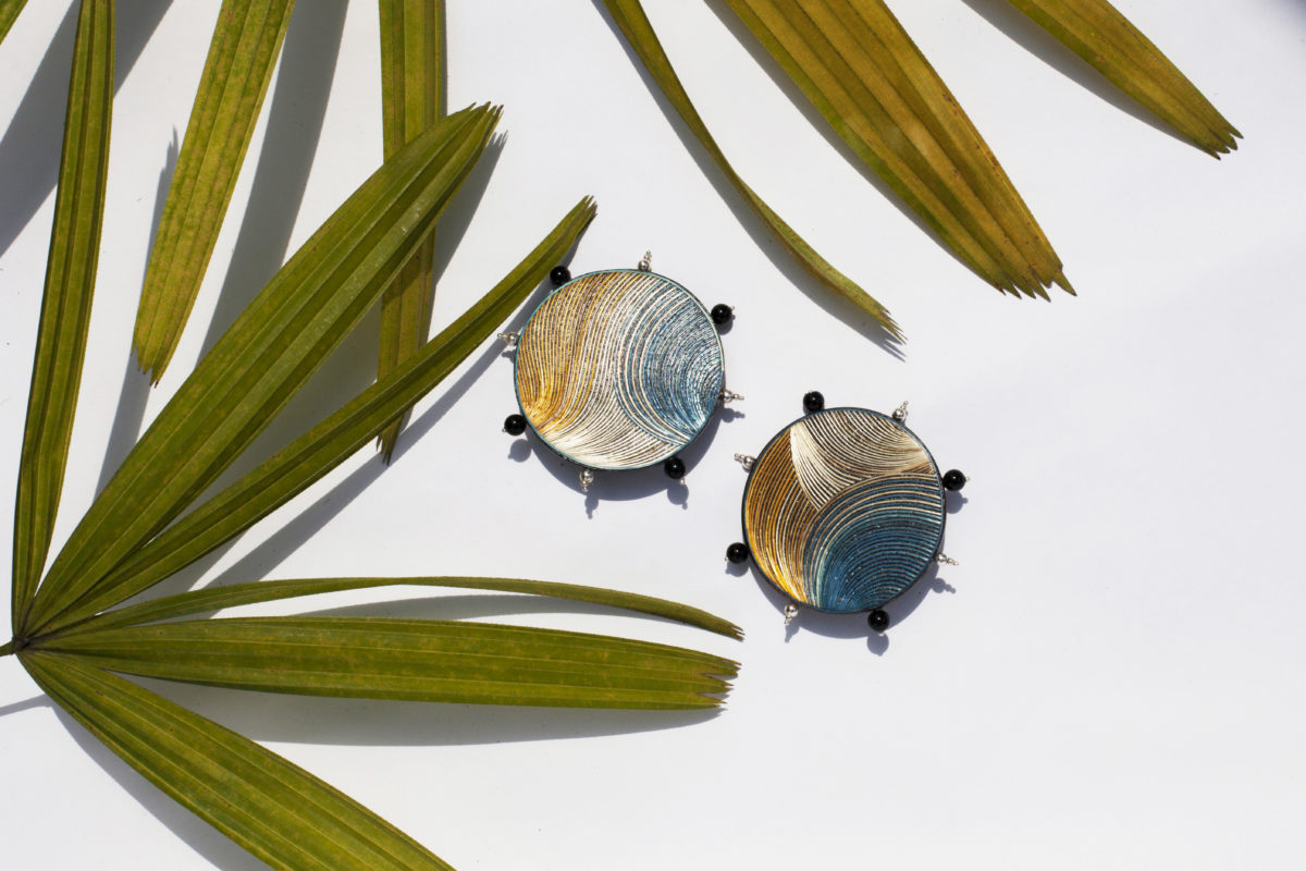 BLUE, WHITE AND YELLOW DISCO EARRINGS MADE WITH THE ENCHAPE EN TAMO TECHNIQUE FROM PASTO IN A TROPICAL SETTING OF GREEN LEAVES