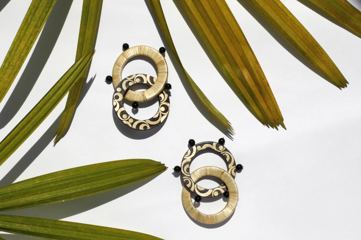 DOUBLE HOOP BLACK AND WHITE EARRINGS MADE WITH THE ENCHAPE EN TAMO TECHNIQUE FROM PASTO IN A TROPICAL SETTING OF GREEN LEAVES