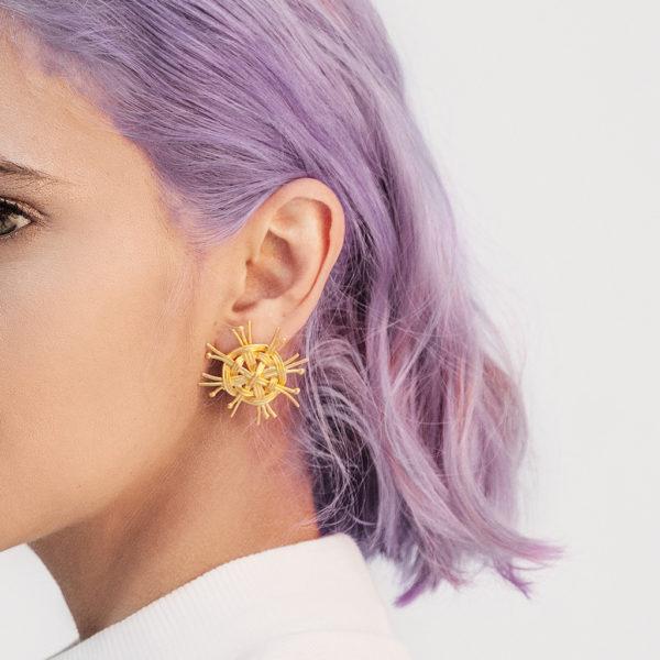 Modelo con pelo morado utilizando Topos tejidos como los fondos de los canastos en plata con baño en oro Parte de la Colección 5 de Aysha Bilgrami Joyeria