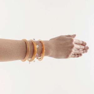 modelo con tres pulseras triangulares en doradas, lisa, piedras semi preciosas y esferas. Parte de la Colección No.7 de Aysha Bilgrami Joyeria