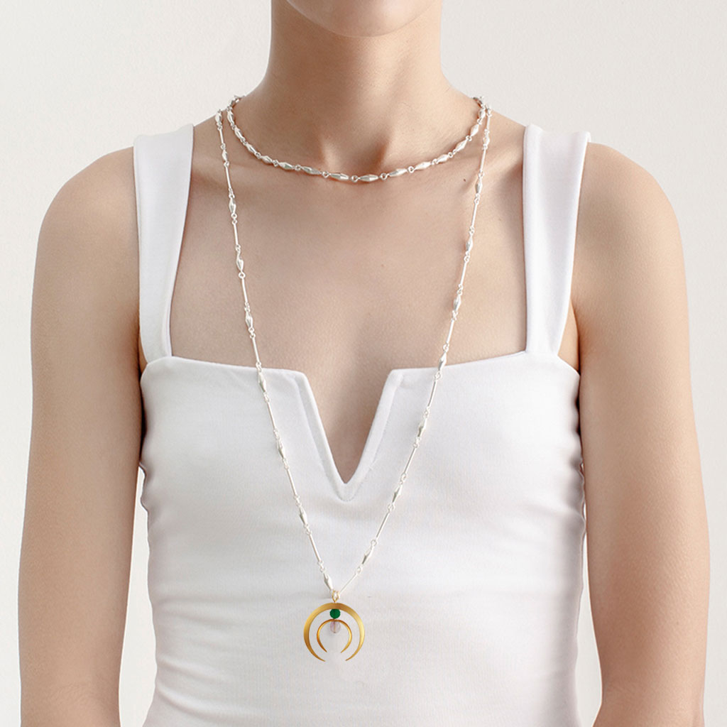 GIRL WEARING BEAUTIFUL NECK MESS OF TWO SILVER CHAINS AND A GOLDEN DOUBLE HALF MOON CHARM