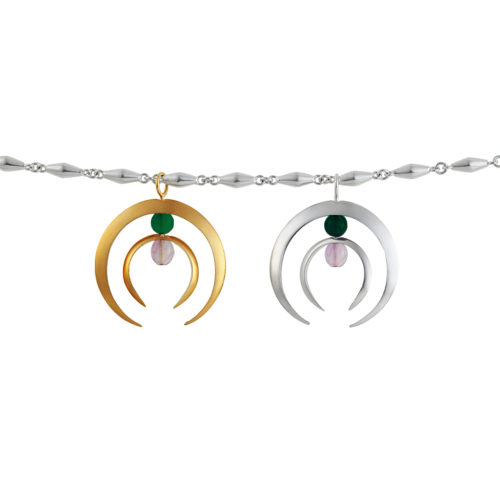identical silver charm and gold charm composed of two half moons and pink and green stone hanging over a piramidal link chain . Jewelry by Aysha Bilgrami