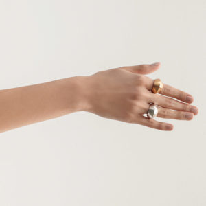 Modelo con Dos anillos voluminosos en plata y plata con baño en oro. Parte de la Colección 7 de Aysha Bilgrami Joyeria