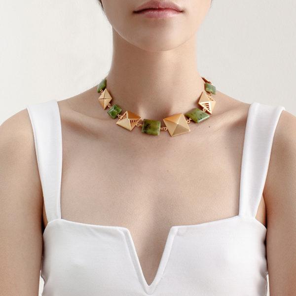 modelo con Collar corto dorado de piezas cuadradas y jade Canadiense, inspirado en los chumbes de los Inga de Putumayo.