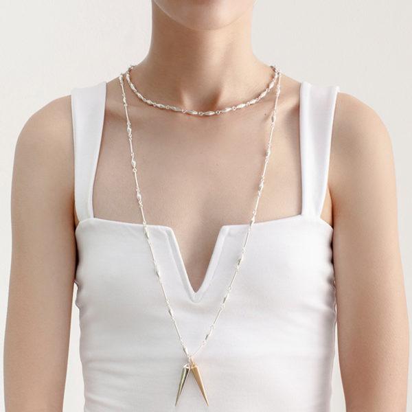modelo usando dos cadenas con eslabones conicos en plata y dijes varios. Parte de la Colección No.7 de Aysha Bilgrami Joyeria.