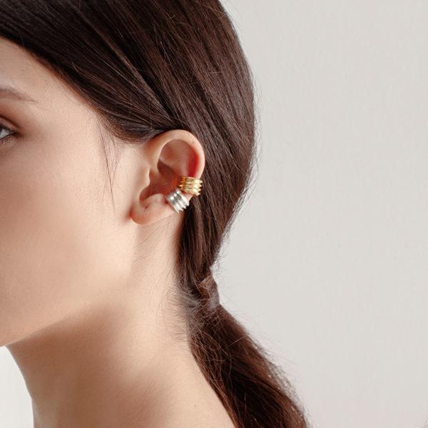 Modelo utilizando dos orejeras gruesas compuestas de texturas triangulares en plata y plata con baño en oro Parte de la Colección 7 de Aysha Bilgrami Joyeria