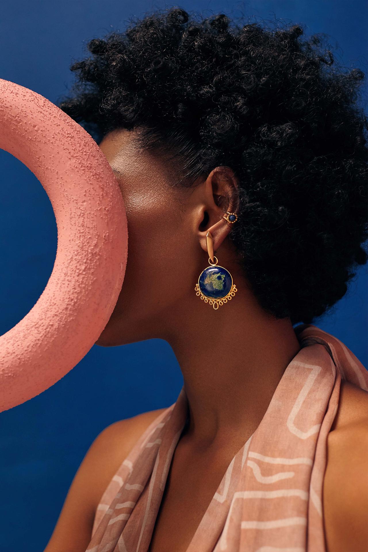 Modelo con vestido rosado y pieza circular rosada. Aretes dorados con piedra semi preciosas. Imagen de Campaña de Colección No.8  de Aysha Bilgrami Joyeria por Daniella Benedetti