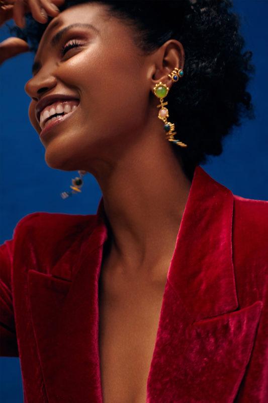 Modelo sonriente con blazer en terciopelo fucsia y aretes y orejeras coloridos en movimiento. Parte de la Colección 8 de Aysha Bilgrami Joyeria. magen de Campaña de Colección No.8  de Aysha Bilgrami Joyeria por Daniella Benedetti