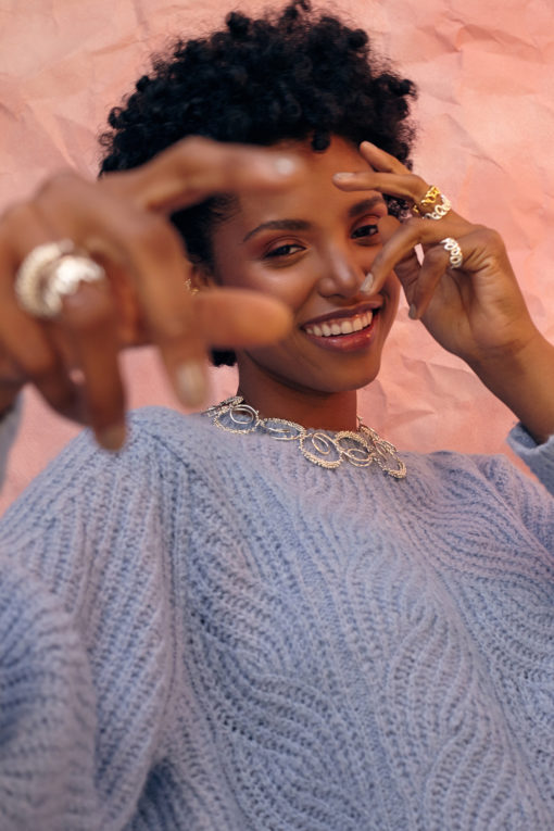 Modelo bailando con saco de lana azul utilizando collar y anillos de la Colección no.8 de Aysha Bilgrami. Campaña de Colección No.8 de Aysha Bilgrami Joyeria por Daniella Benedetti