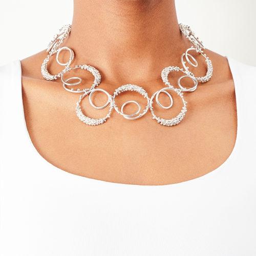 modelo con collar plateado inspirado por la forma del sonido de la vocal 'O' de los alfabetos español y ruso. Parte de la Colección No.7 de Aysha Bilgrami Joyeria