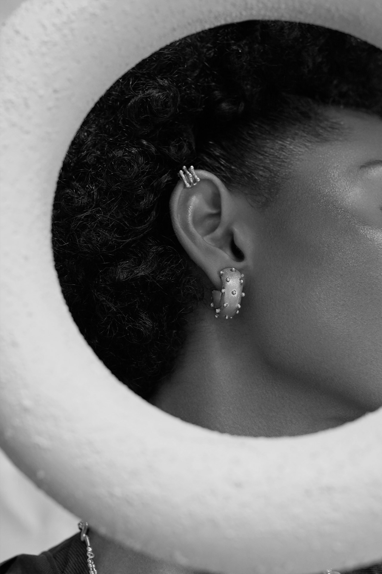 black and white portrait of lady wearing chunky hoops and earcuffs